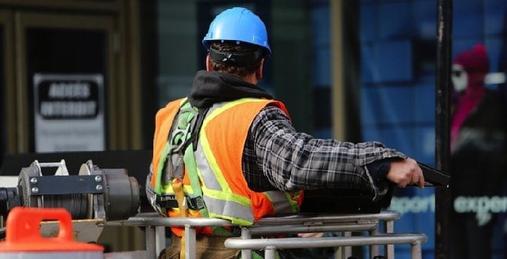 Image of construction worker onsite with hard hat performing safety reporting